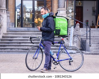 GHENT, BELGIUM. MAY 1, 2018. Uber eats rider with race bike or bicycle holding phone in hands with earphones and uber eats bag. Uber Eats is online food ordering and delivery platform. Ghent, Belgium.