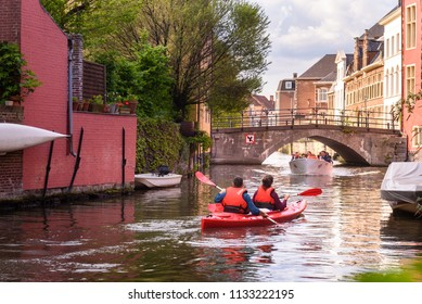 GHENT, BELGIUM. May 1, 2018: People on kayak and tourists in a boat on canal in historical city center of Ghent behind the Gravensteen castle in Ghent, Flanders, Belgium.