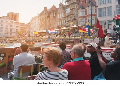 Ghent, Belgium. May 21, 2016. Sun-illuminated excursion boats with tourists on the background of the flags of different countries.