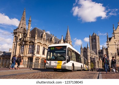 GHENT, BELGIUM. Sept. 28, 2018. Bus of Belgian public transport company De Lijn in historical city center of Flemish city Ghent. Famous bridge with historical buildings in background. Ghent, Belgium.