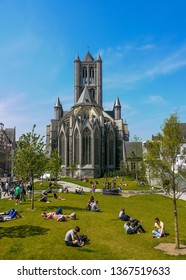 Ghent, East Flanders / Belgium - May 6th, 2013: People sitting on grass behind Saint Nicholas' Church