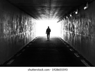Ghent, Flanders, Belgium - 02 20 2021: Concept photo of a male man walking through a dark tunnel