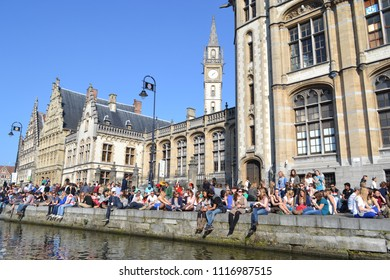 Ghent/Belgium- 03/19/2012: Students relax by the canal on a pleasant Spring afternoon in Ghent.