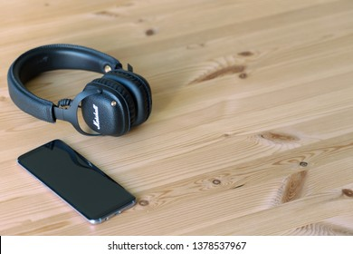 GHENT/FLANDERS/BELGIUM - April 22, 2019: Bluetooth headphone and smartphone on a wooden table. Dark vintage Marshall headphone connected to device.