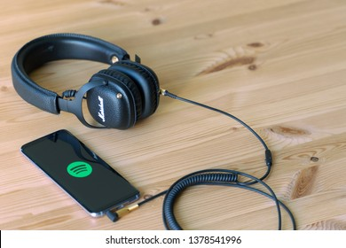 GHENT/FLANDERS/BELGIUM - April 22, 2019: Bluetooth headphone connected to smartphone for music streaming. Dark retro headphone and modern devices.