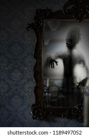 A ghost appears in an old vintage mirror. Spooky, creepy shadow. Phantom apparition.
