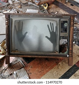 Ghost emerges through broken flickering television screen in haunted house.