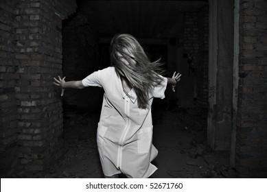 Ghost of girl in dark corridor