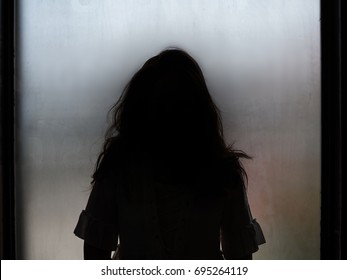 Ghost girl silhouette standing in front of window