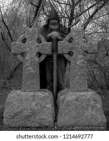 A ghost of a hooded knight with a sword standing behind Celtic grave markers at dusk. Black and white.