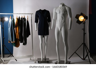 Ghost mannequins, clothes and professional lighting equipment in modern photo studio
