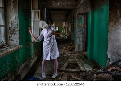 A ghost nurse or a zombie nurse or doctor with a bandaged head and a face without eyes and mouth stands inside an abandoned and destroyed clinic or asylum and holds a syringe in her hand. Horror scene