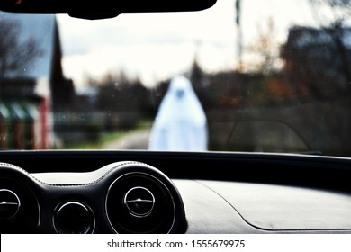 Ghost on the road. Bringing in front of car. Driver saw white ghost in front of hood. Otherworldly creature scares people on the track. Restless soul walks.Phantom of dead man in white