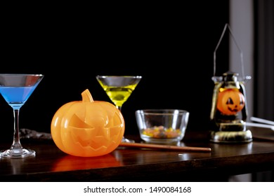 Ghost pumpkins, candies, and drinks on the table at the Halloween party in the night on dark background.