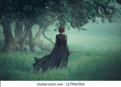 ghost red hair girl walking dark forest, long black dress train waving flying fluttering wind. Gothic queen witch. art photo green colors, emerald trees grass, fog fabolous vintage style halloween