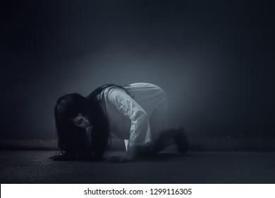 Ghost Woman Horror scene Death movie with Halloween Makeup lying on Floor in Darkroom.