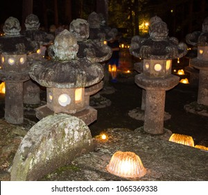 A ghostly figure of a boy stands among stone lanterns glowing on a dark night at the entrance to a centuries old Buddhist cemetery in Japan during the obon ('return of dead spirits') summer festival.
