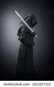 Ghostly figure with medieval sword in the dark with clipping path