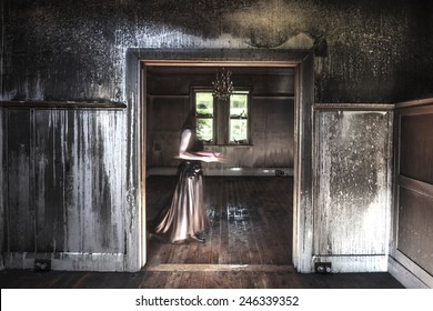 Ghostly figure reading a book in a fire damaged house.