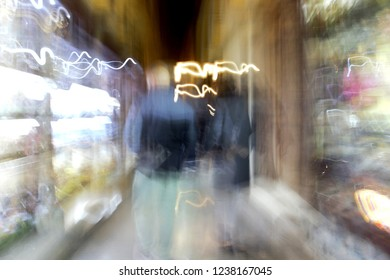 ghostly human figures in old commercial street of Granada, Shopping, night photo, photographic sweep, sensation of movement, blurred people, impressionist photography, abstract, nightlife, atmosphere,