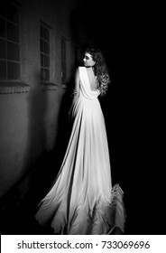 Ghostly portrait of beautiful brunette woman in vintage white dress, standing in a shadowed room, with her own shadow reflecting on the wall.