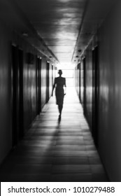 Ghostly silhouette walking down a creepy hallway, from the light to shadow
