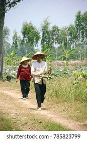 An Giang province, Vietnam - April 19, 2015: Old countrymans walking on country road in western of Vietnam