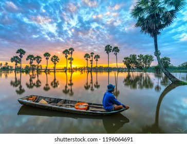 An Giang, Vietnam - September 13, 2018: Unidentified fishers sit on a boat watching the dawn greeting the new day in his hometown with the scenic landscape around in rural An Giang, Vietnam.