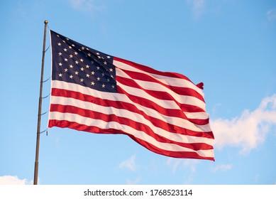 Le Drapeau Américain géant vole haut contre un ciel bleu clair avec quelques petits nuages avec place pour texte.