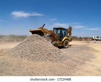 A giant backhoe is shoveling and dumping gravel on a desert excavation site.  Horizontally framed shot.