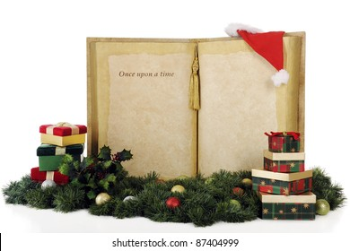 """A giant book with the words, """"Once upon a time..."""" with plenty of space for your copy.  The books is surrounded by Christmas gifts, decor and Santa's hat.  On a white background."""