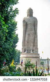 Giant Buddha Statue in Wat Thai Sarnath Buddhism Temple near Varansasi in Uttar Pradesh, India. The 80 feet sculpture is in Buddhist temple and gardens complex. Sarnath, India - November 7, 2018