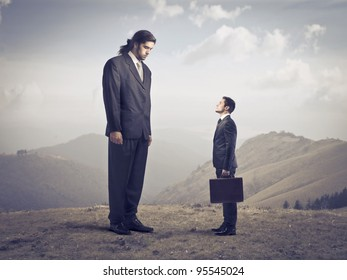 Giant businessman observing a smaller one
