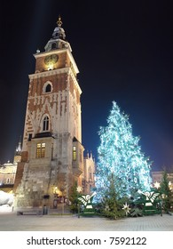 Giant christmas tree illuminated at night standing next to historical Town Hall tower on the Main Market Square in Krakow