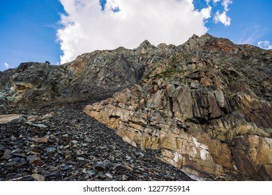 Giant cloud above ridge. Unusual rocky mountainside with vegetation. Amazing mountain range under blue cloudy sky. Wonderful rocks. Atmospheric landscape of majestic nature of highlands.
