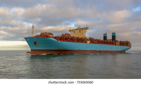 Giant container ship sailing on the North Sea from China to Germany seen from side