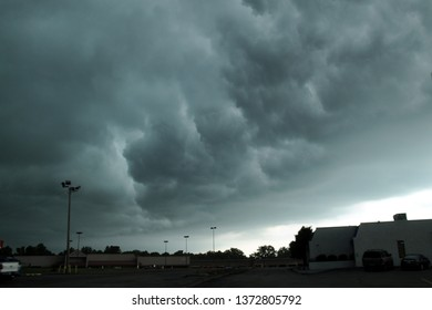 giant dark ominous thunderstorm clouds in the sky overhead up above a shopping mall, strip mall parking lot