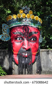 A giant decorative mask sculpture in an outdoor themepark