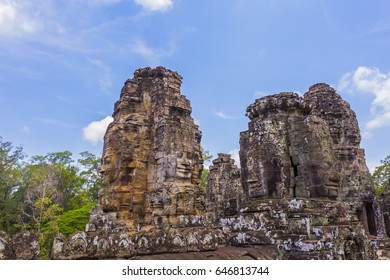 "The giant faces on the towers. known as ""face towers"" contain four very large heads on top of the gates facing each of the four cardinal directions at Bayon temple.This is a famous tourist attraction."