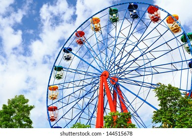 Giant ferris wheel against blue sky and white cloud which mean an amusement-park or fairground ride consisting of a giant vertical revolving wheel with passenger cars suspended on its outer edge