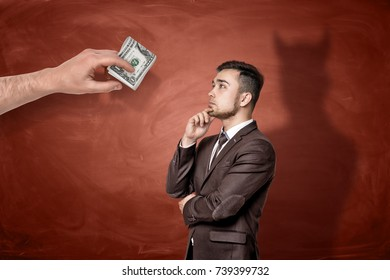 A giant hand with a roll of dollar bills in front of a thinking businessman who cast a shadow of a devil. Business and money. Temptation of crime. Unlawful gain.