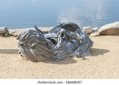 Giant head of the Awakening cast iron sculpture half buried in sand at National Harbor, Virginia