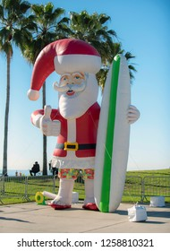 Giant inflatable Santa Claus stands near palm trees at beach park holding surfboard. Christmas holiday celebrated in warm tropical weather