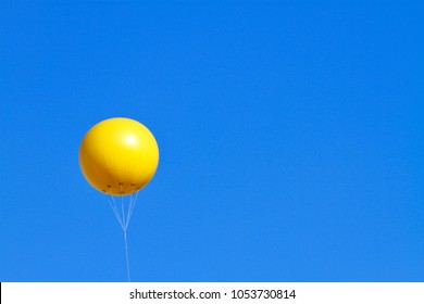 A giant inflatable yellow advertising balloon floats in the sunny blue sky.
