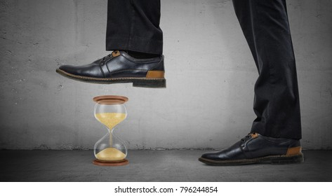 Giant male legs in shiny boots stand on concrete background and step on a small hourglass. Work in deadline. Crash time wasters. Results against timetable.
