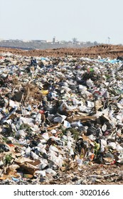 A giant mound of trash in a landfill. All trademarks and logos digitally removed.