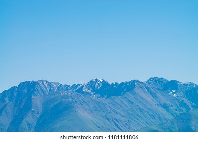 Giant mountains and glaciers. Snowy ridge under blue clear sky. Snow summit in highlands. Permafrost, permanent cold. Amazing atmospheric minimalist mountain landscape.