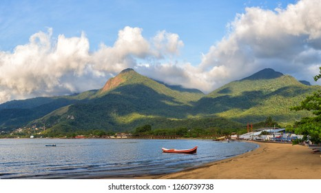 Giant mountains on the island, fisherman's canoe on the beach.