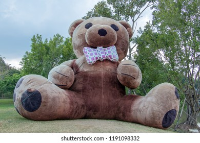 The giant plush teddy bear sitting on a green meadow in the garden.
