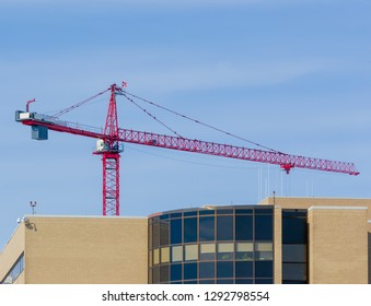 Giant red, white and blue construction cranes at a site building a medical center with heavy equipment, cars and workers-Kentucky 2019-urban exploration photography industrial
